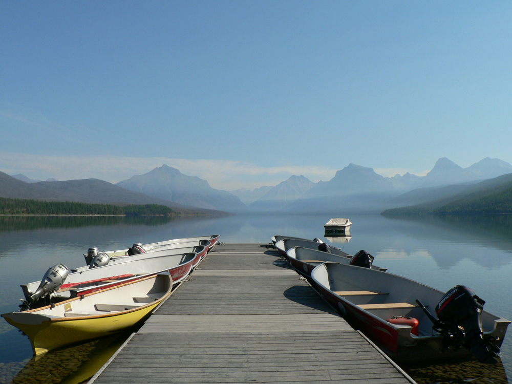 View of Lake McDonald in Glacier National Park during a family visit in August 2007 showing a dock with boats along both sides and a clear blue sky with shorelines and mountains in the distance